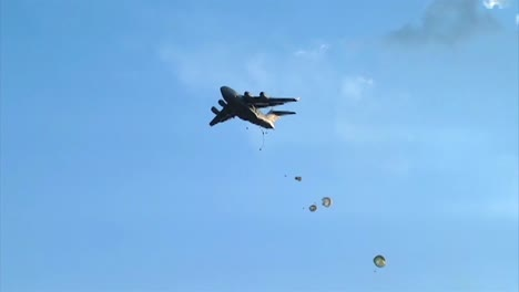 Ground-Angle-View-Of-Paratroopers-Airdropped-And-Parachuting-To-Earth-From-A-C18