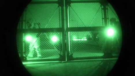 Night-Vision-Of-Men-In-Biohazard-Suits-Entering-An-Industrial-Area