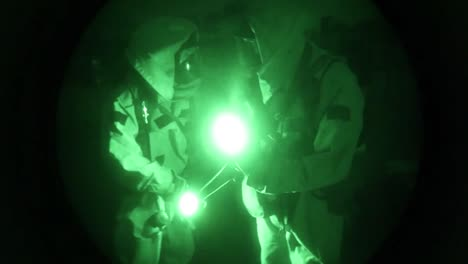 Night-Vision-Of-Men-In-Biohazard-Suits-Entering-An-Industrial-Area-And-Searching-For-Chemical-Leaks