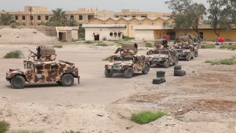 Un-Convoy-De-Vehículos-Militares-Se-Mueve-A-Través-De-Una-Región-Destruida-De-Irak