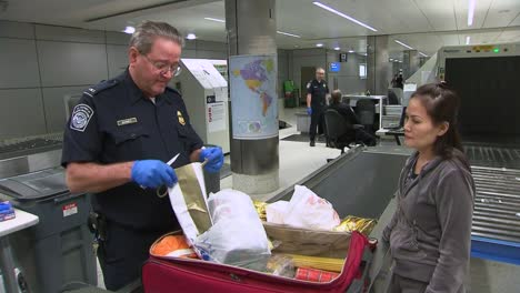 Passengers-Coming-Into-An-International-Airport-Terminal-Have-Bags-Inspected-By-Us-Customs