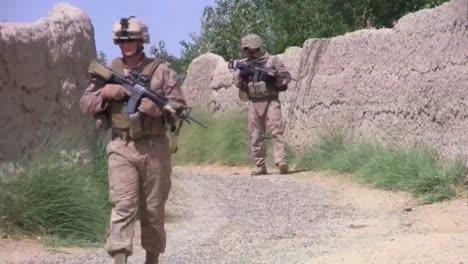 Los-Infantes-De-Marina-En-Patrulla-Caminan-Por-Campos-Y-Tierras-De-Cultivo-En-Afganistán-Con-Niños-Pequeños-Siguiendo
