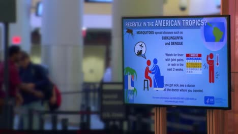 Travelers-At-An-Airport-Are-Warned-Of-Infectious-Diseases-In-Regions-They-May-Have-Traveled-To
