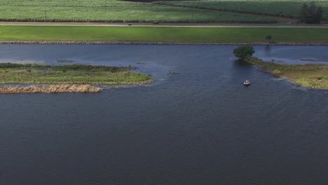 Good-Aerial-Over-Three-Fishermen-In-A-Small-Boat-Moving-Along-A-River