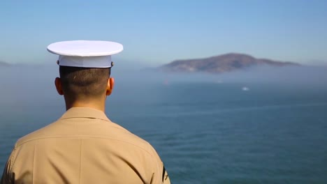 A-Navy-Ship-Passes-By-San-Francisco-Landmarks-Including-Alcatraz-And-The-Bay-Bridge