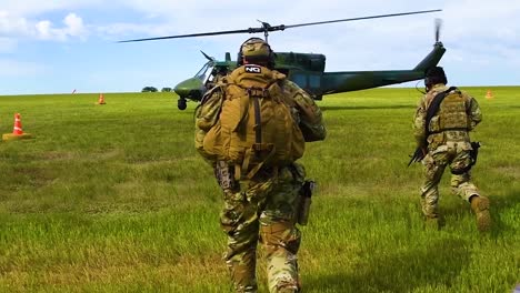 Soldiers-Run-To-A-Huey-Helicopter-On-A-Grassy-Plain-With-Us-Servicement-And-Forces-Guarding-The-Mission-In-Slow-Motion