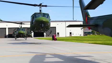 Ein-Geschwader-Von-Huey-Hubschraubern-Steigt-In-Zeitlupe-Von-Einem-Luftwaffenstützpunkt-Auf