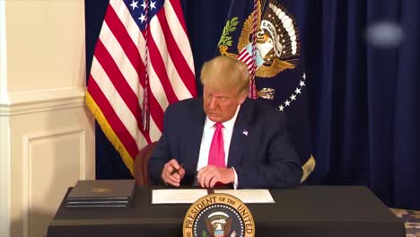 Us-President-Donald-Trump-Signs-A-Generic-Bill-And-Shows-It-To-Everyone