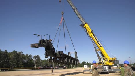 A-Crane-Prepares-To-Lift-A-Trailer-Of-1158th-Transportation-Company-Of-Wisconsin-National-Guard-Onto-A-Rail-Car-3