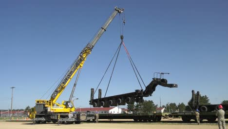A-Crane-Prepares-To-Lift-A-Trailer-Of-1158th-Transportation-Company-Of-Wisconsin-National-Guard-Onto-A-Rail-Car-4