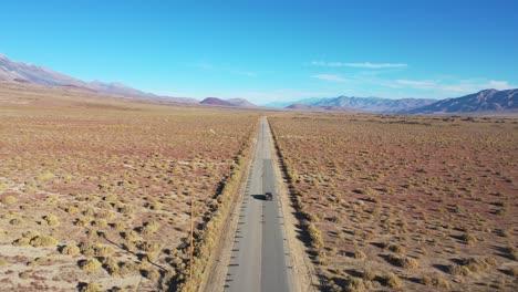 La-Antena-De-Un-Vehículo-Con-Tracción-En-Las-Cuatro-Ruedas-En-Una-Carretera-Pavimentada-A-Través-De-La-Región-Desértica-Del-Valle-De-Owens-Sugiere-Una-Aventura-Remota-En-La-Sierra-Oriental