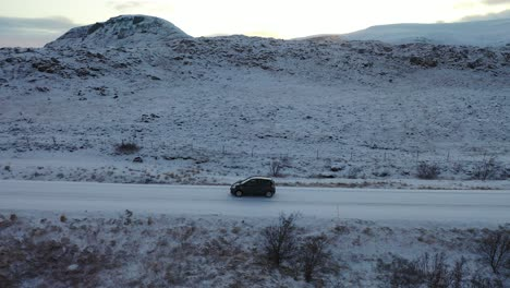 Aerial-of-a-car-driving-a-long-a-road-on-the-wintry-Icelandic-countryside