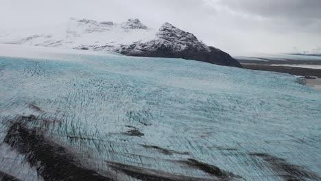 Antena-De-Un-Glaciar-Congelado-Por-Una-Cordillera-Nevada-En-Islandia