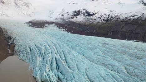 Vista-Aérea-of-a-glacier-frozen-by-a-snowcovered-montaña-range-in-Iceland-1