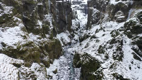 An-aerial-view-snaking-through-the-Mulagljufur-Canyon-leads-to-the-Mulafoss-waterfall-in-Austurland-Iceland