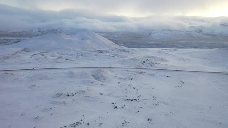 Aerial-of-cars-driving-along-a-snowcovered-highway-by-mountains-in-Iceland
