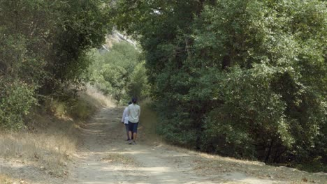 A-Braille-Institute-teacher-helps-a-blind-student-use-her-white-cane-to-walk-on-a-dirt-road-in-the-woods-California