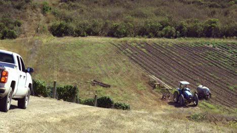 A-pickup-truck-drives-down-a-farm-road-on-the-edge-of-a-vineyard-in-the-fertile-ground-of-the-Lompoc-Valley-California