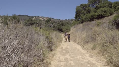 A-father-and-son-bond-their-friendship-and-relationship-while-walking-on-a-wilderness-trail-Gaviota-Coast-California