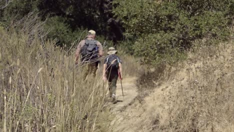 A-father-and-son-bond-their-friendship-and-relationship-while-walking-on-a-wilderness-trail-Gaviota-Coast-California-1