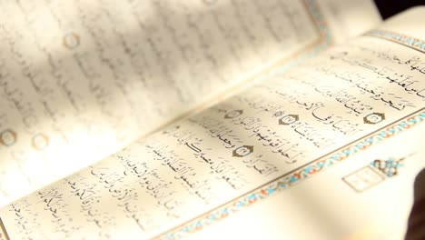 Young-Muslim-Man-Reading-Quran-In-Mosque-Using-Finger-As-A-Guide