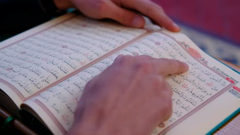 Close-Up-of-Hands-on-Quran-In-Mosque-1