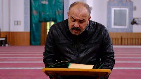 Middle-Age-Man-Reading-The-Quran-In-Mosque