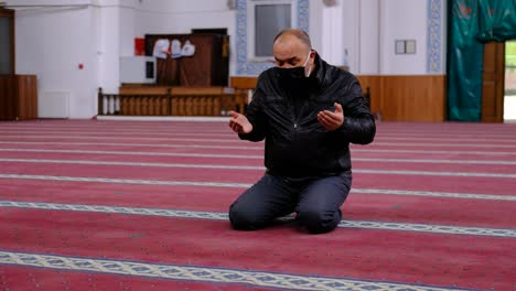 Old-Man-Wearing-Mask-Raising-His-Hands-And-Praying-In-The-Mosque