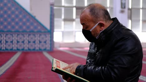 Older-Man-Wears-Mask-And-Reads-The-Quran-In-Mosque