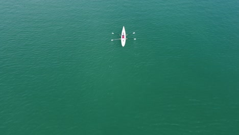 Two-Female-Rowing-Canoe-On-Sea
