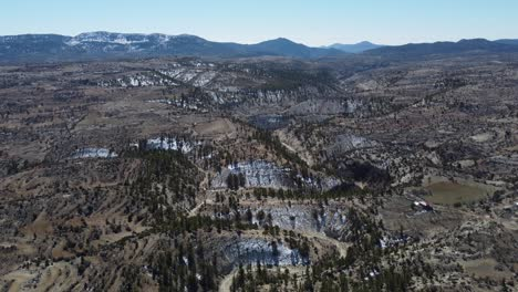 Drone-View-Over-Meandering-Valley-Against-Snowy-Mountains