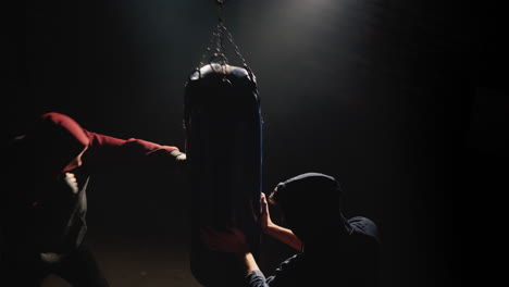 Two-young-fighter-fighters-train-with-a-punching-bag