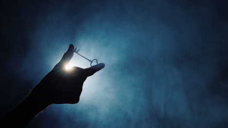 A-man-s-hand-holds-a-key-against-a-dark-background-1