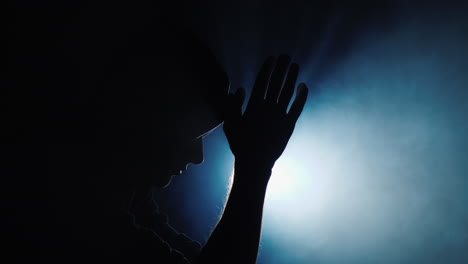 Silhouette-of-a-man-in-a-hood-praying-in-the-dark