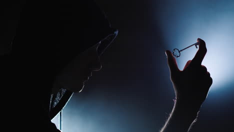 The-silhouette-of-a-man-in-a-hood-with-a-key-in-his-hand