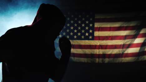 The-silhouette-of-a-fighter-trains-against-the-background-of-the-flag-of-America