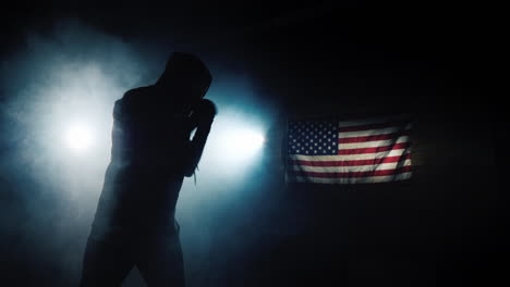 The-silhouette-of-a-fighter-trains-against-the-background-of-the-flag-of-America-1