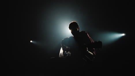 A-young-man-plays-the-guitar-sits-on-stage-4