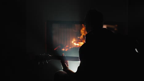 A-young-man-plays-the-guitar-by-a-fireplace