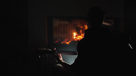 A-young-man-plays-the-guitar-by-a-fireplace-1