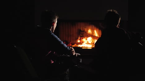 Two-guys-playing-the-guitar-by-the-fireplace