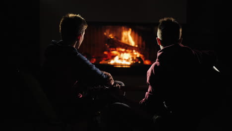 Man-plays-guitar-by-the-fireplace-next-to-a-friend