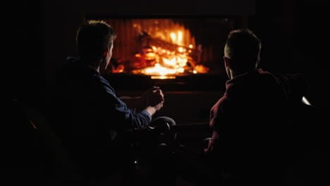 Friends-rest-at-home-by-the-fireplace-and-a-man-plays-the-guitar