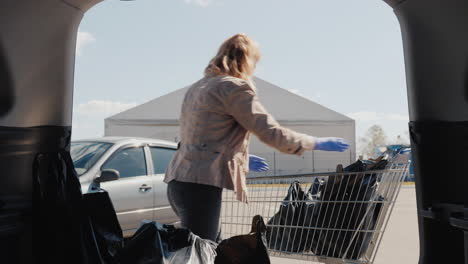 A-Woman-In-A-Mask-And-Gloves-Puts-Shopping-Bags-In-The-Trunk-Of-A-Car