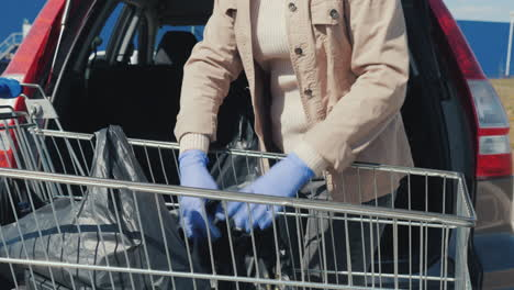 Man-In-Protective-Gloves-Puts-Shopping-Bags-In-The-Trunk-Of-The-Car