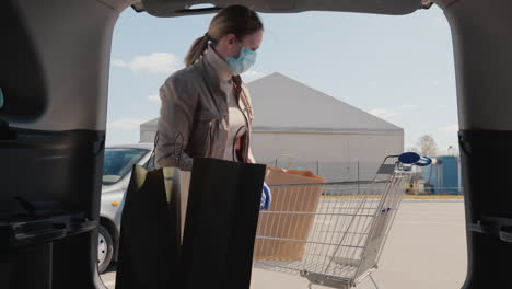 Shopping-During-The-Epidemic---A-Woman-Puts-Bags-Of-Food-In-The-Trunk-Of-A-Car