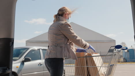 Shopping-During-The-Epidemic---A-Woman-Puts-Bags-Of-Food-In-The-Trunk-Of-A-Car-1