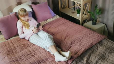 Teenage-girl-uses-a-smartphone-in-her-bedroom