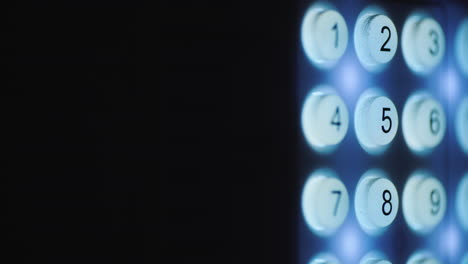 A-person-enters-a-pin-code-on-a-backlit-keyboard