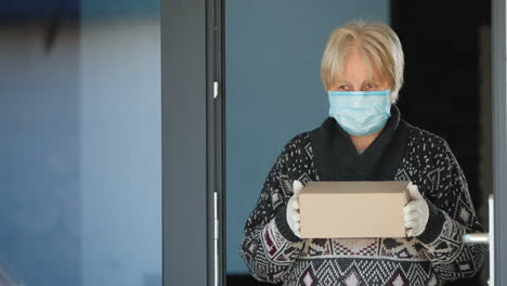 An-Elderly-Masked-Woman-Stands-On-The-Doorstep-Of-The-House-And-Holds-A-Small-Parcel-In-Her-Hands